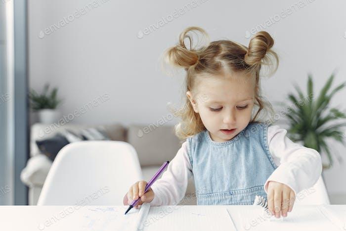 Kleines Mädchen sitzt auf einem Tisch mit Büchern