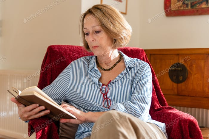 Elegant mature woman is reading a book at home