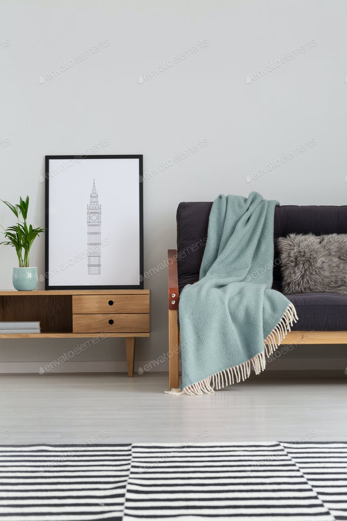 Vertical view of sofa with pastel blue blanket next to wooden ca