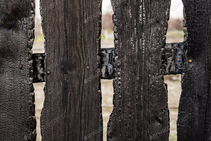 Burnt fence boards after a fire in a private house
