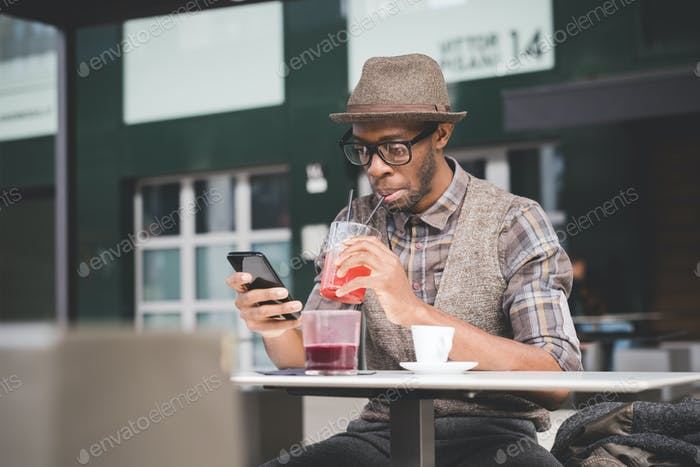 young handsome afro black man sitting on a table, smartphone han