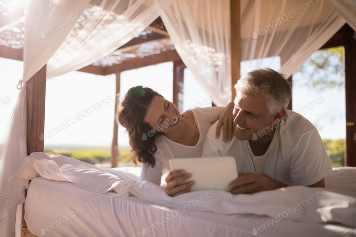 Happy couple using digital tablet on bed