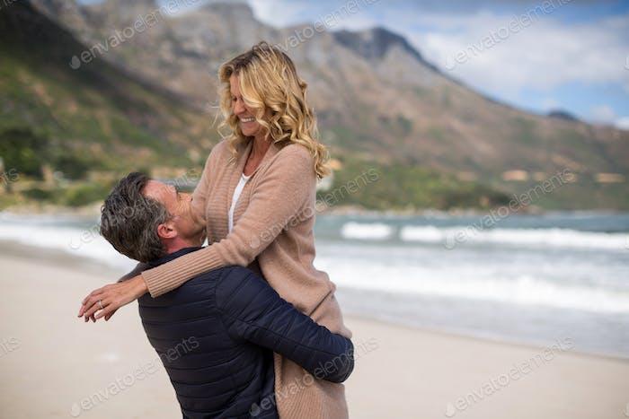 Mature man holding mature woman on beach