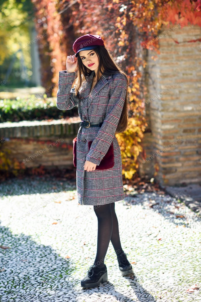 Young beautiful woman with very long hair wearing winter coat and cap in autumn leaves background