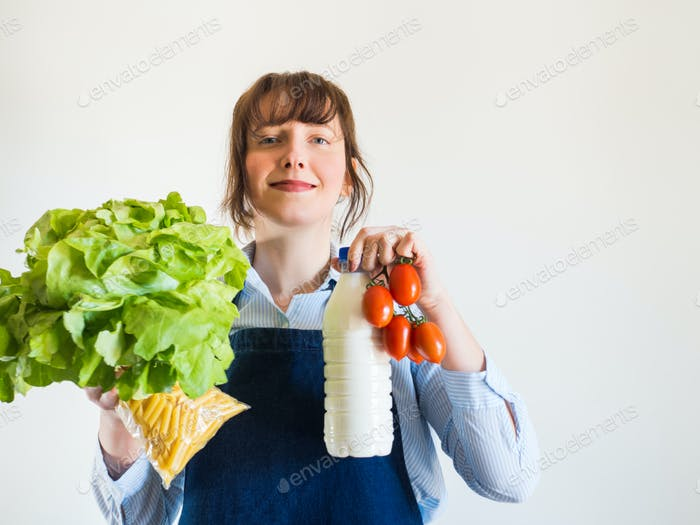 Woman in blue apron with food staples in hand
