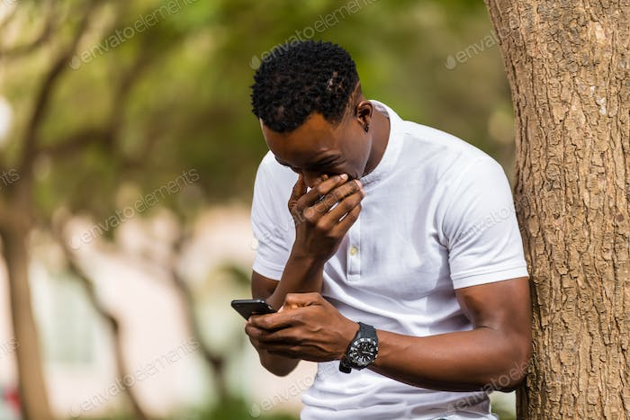 Outdoor portrait of a Young black African American men texting