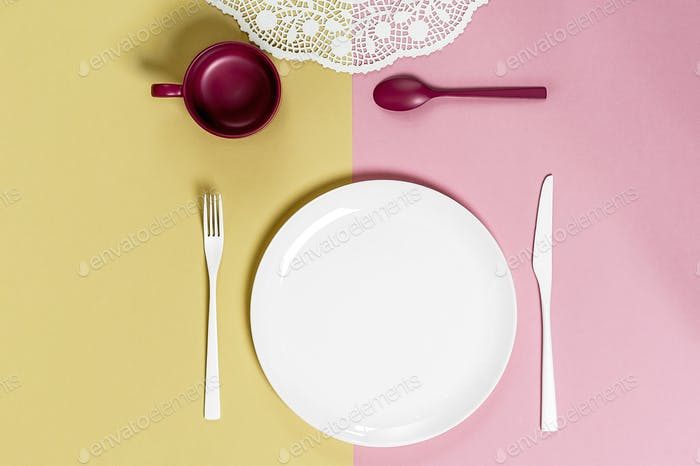 White round plate and cutlery on a light pink-green background.
