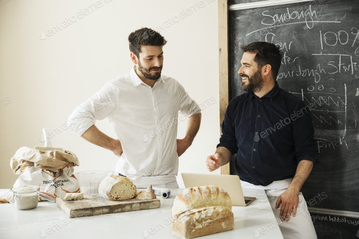 Two bakers using a laptop, product development