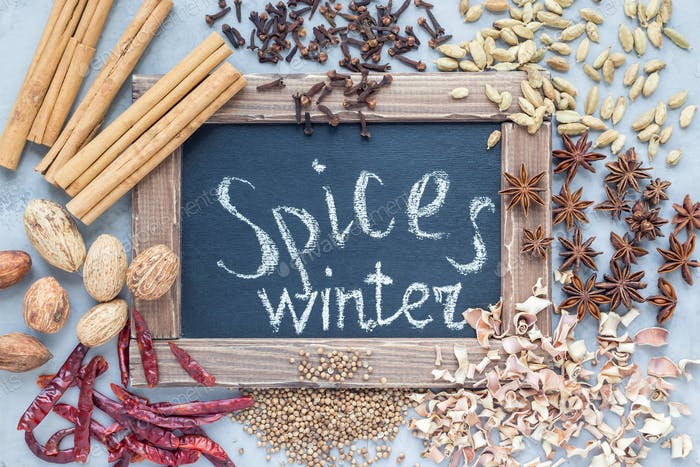 Aromatic winter spices around chalk board on gray concrete background, top view, horizontal