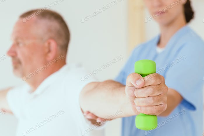 Physiotherapist assisting a senior patient performing weight exercises