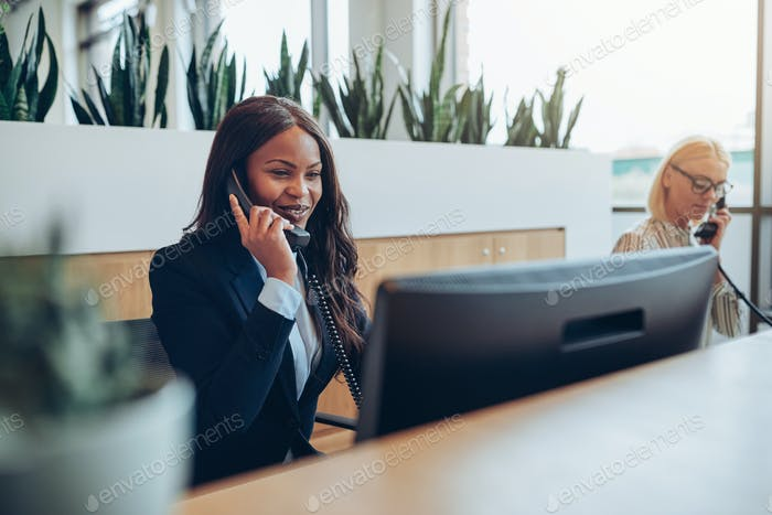 Two smiling businesswomen talking on telephones at an office reception