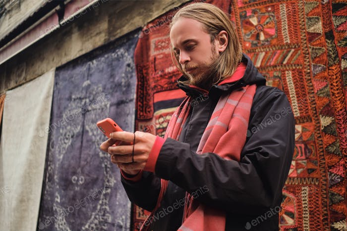 Young stylish tourist man confidently using smartphone during walk through local market