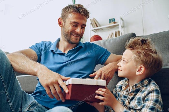 Kleiner Sohn gibt seinem Vater eine Geschenkbox zum Vatertag
