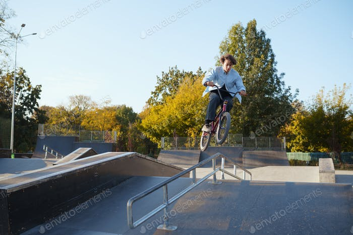 Bmx biker rides by railing in skatepark