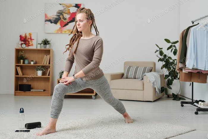Young barefoot woman in activewear stretching legs while exercising on carpet