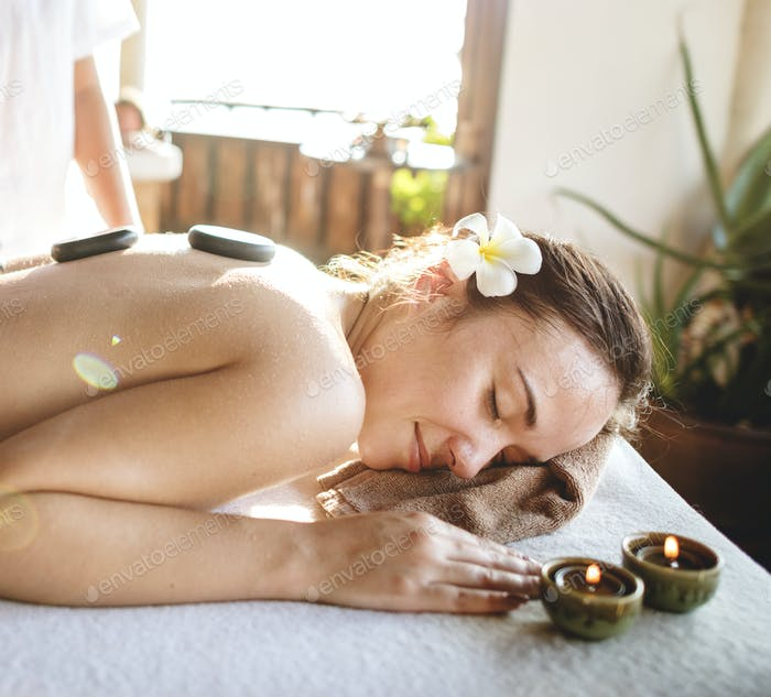 Woman in massage therapy with stones on the back