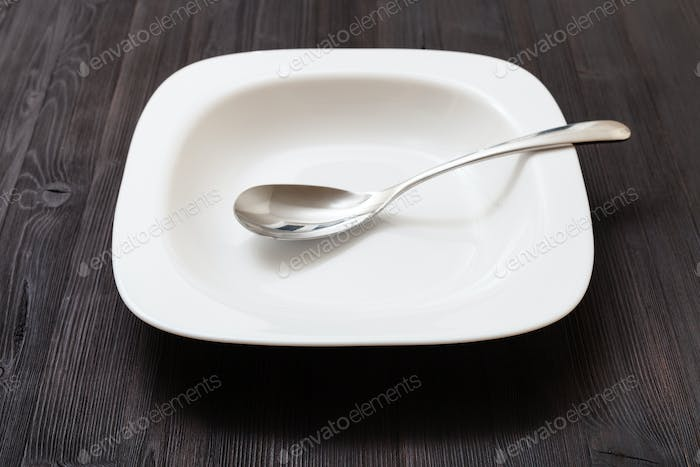 white bowl with spoon on dark brown board