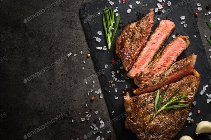Grilled beef steak on black table