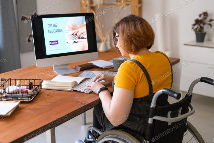 Young female in wheelchair pressing keys on keypad in front of computer monitor