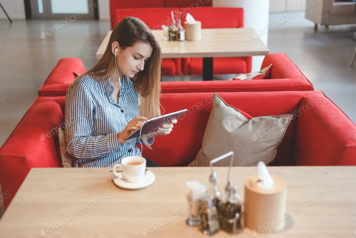 Candid image of young woman using tablet computer in a cafe