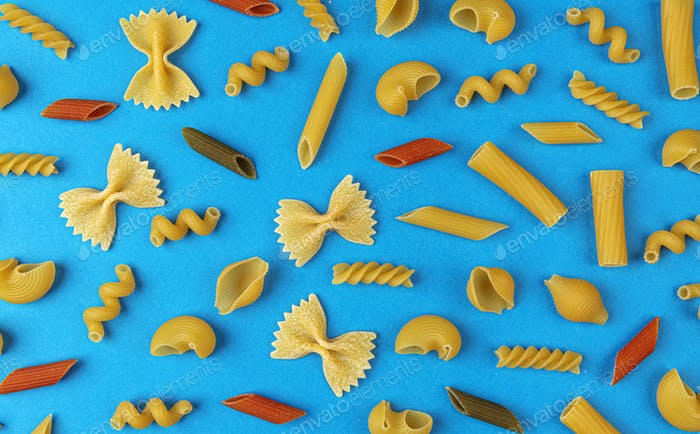 Different pasta types on blue background, top view, flat lay composition