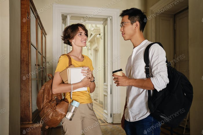Two young attractive international students happily talking in corridor of university