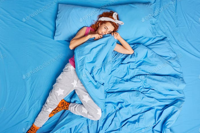 Top view of happy redhead European woman dressed in pajama hides under soft blanket lying in bed awa