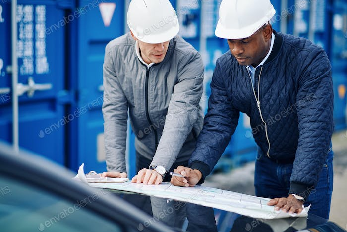 Two shipping engineers leaning on a truck discussing blueprints