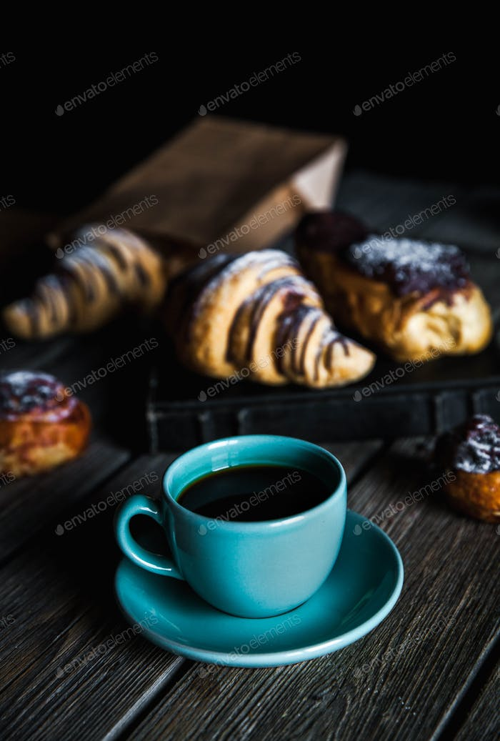 Croissant and white cup of black coffee on brown canvas