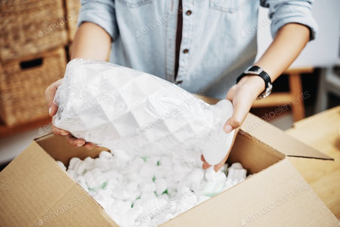 Woman packing vase in box