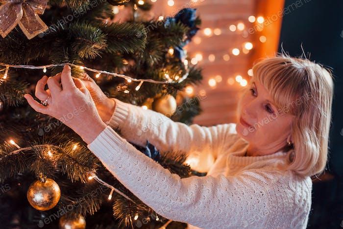 Senior glückliche Frau schmückt Weihnachtsbaum im neuen Jahr dekorierten Raum
