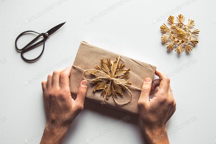 Man hands give wrapped christmas holiday handmade present in paper with red ribbon. Present box