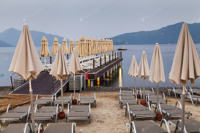Evening view of the pier with sun loungers and parasols.