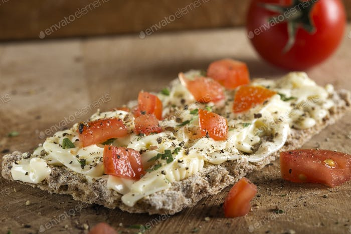 Crispbread with melted cheese and pieces of cherry tomatoes