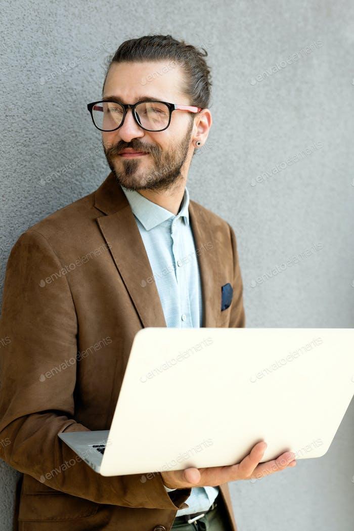 Портрет молодого человека с помощью ноутбука открытый городской