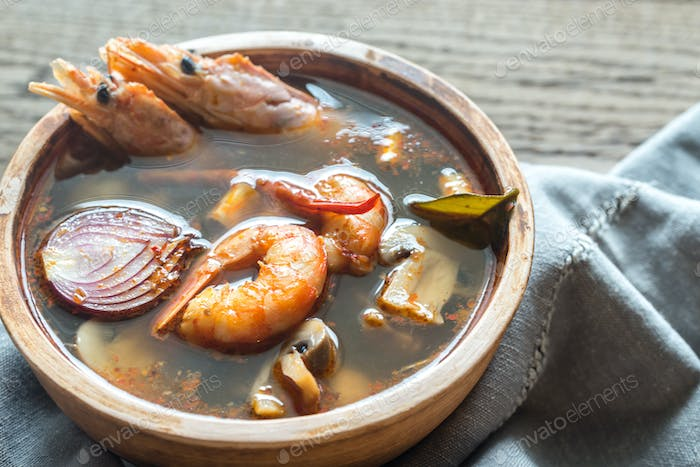 Bowl of thai tom yum soup on the wooden table