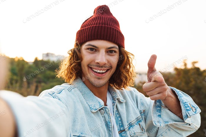 Cheerful young curly man taking a selfie by camera