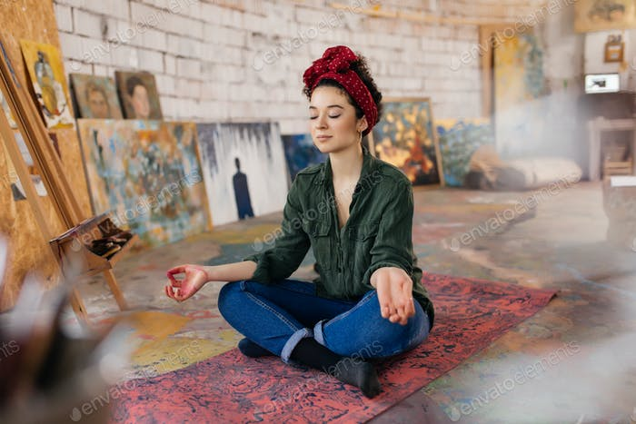 Young attractive smiling woman with closing eyes sitting on yoga