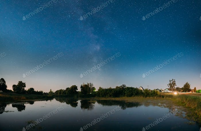 Night Starry Sky With Milky Way Galaxy Above Russian Village. Ni