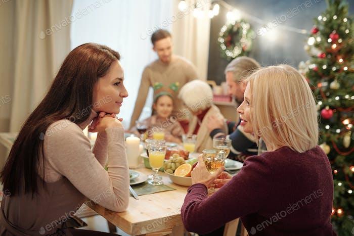 Entspannte junge und reife Frauen plaudern durch Getränk durch serviert festlichen Tisch