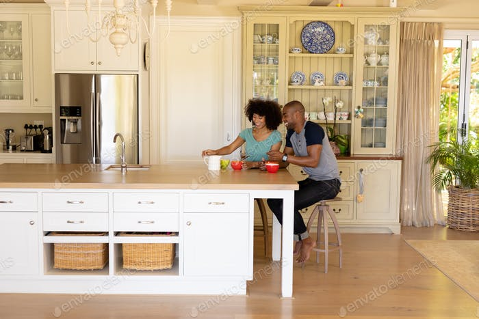 Happy young couple sitting at table in the kitchen