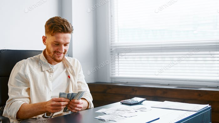 Smiling company manager with beard counts dollars in hands sitting at table