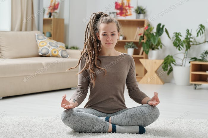 Serene girl in activewear crossing legs while practicing yoga on the floor