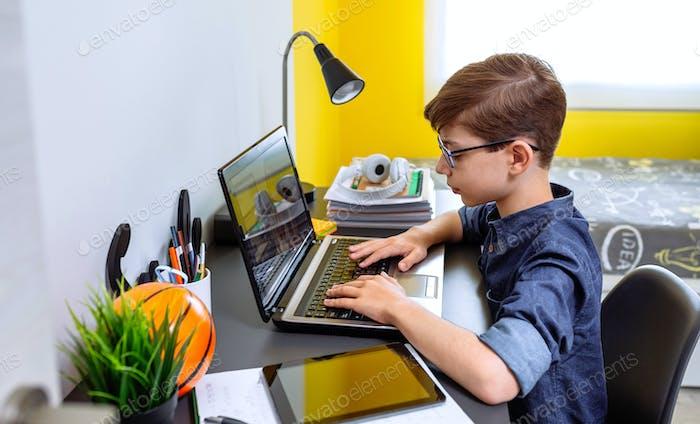 Junge macht Hausaufgaben mit Laptop