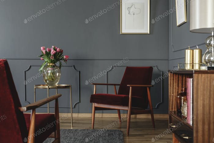Pink flowers on gold table next to red wooden armchair in dark l