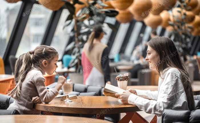 Happy young women mother with children sitting at dinner table and talking in restaurant
