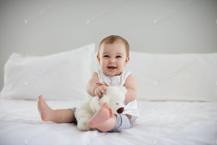 Niedlich Baby Mädchen spielen mit Plüschtier auf Bett