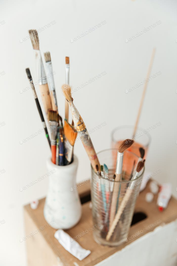 Painting brushes over white wall.
