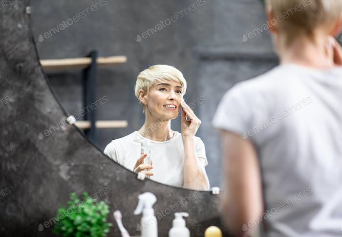Lady Applying Tonic On Cotton Pad Refreshing Skin In Bathroom