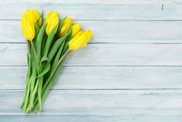Easter card wooden background with yellow tulips